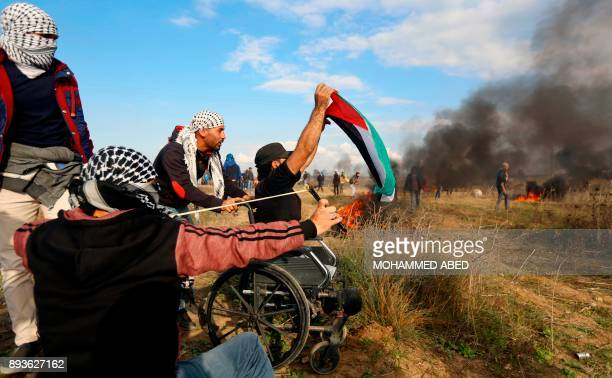 A picture taken on December 15 2017 shows wheelchairbound Palestinian demonstrator Ibrahim Abu Thurayeh waving a Palestinian flag during a protest...