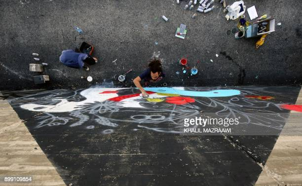 A picture taken on December 16 2017 shows graffiti artists Suhaib Attar and Suha Sultan drawing a mural in the Jordanian capital Amman A tiny group...