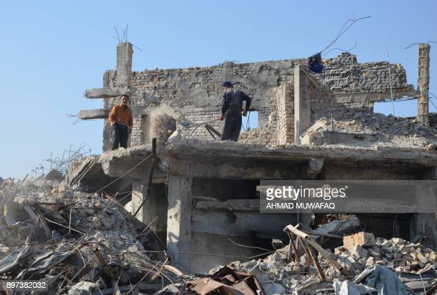 A picture taken on December 16 2017 shows Iraqi volunteers salvaging and cleaning up the debris and destruction in the Bab alSaray area in the old...