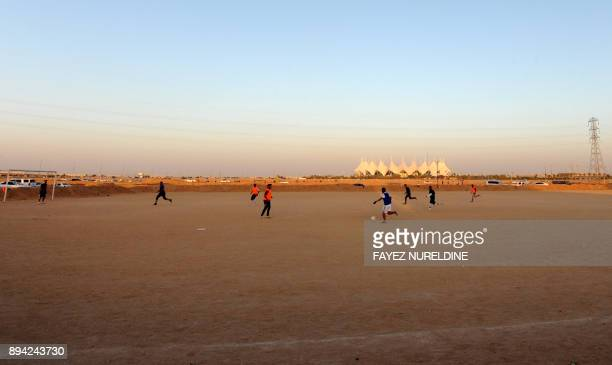 A picture taken on December 16 2017 shows Saudis playing football at a local sandbased pitch in front of the International King Fahad stadium in the...