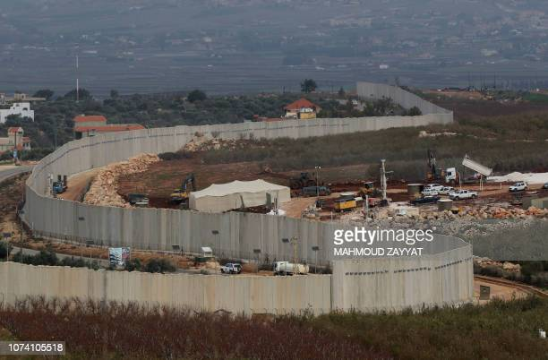 A picture taken on December 16 2018 from the southern Lebanese village of Adaisseh shows members of the Israeli military excavators trailers and...