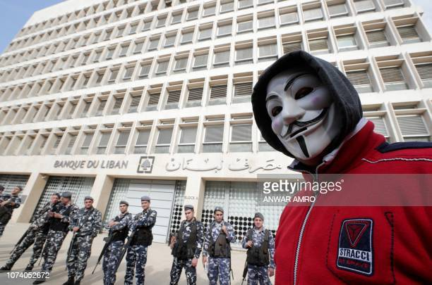 A picture taken on December 16 shows a demonstrator looking on as Lebanese policemen stand guard outside the Central Bank in the capital Beirut