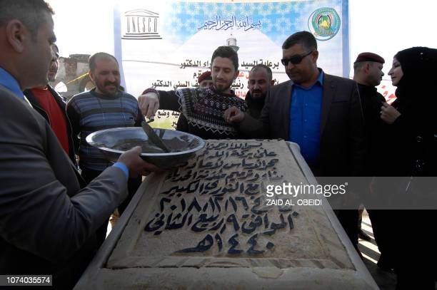 A picture taken on December 16 shows attendees placing the cornerstone for the rebuilding of the Great Mosque of AlNuri and 'AlHadba' leaning minaret...