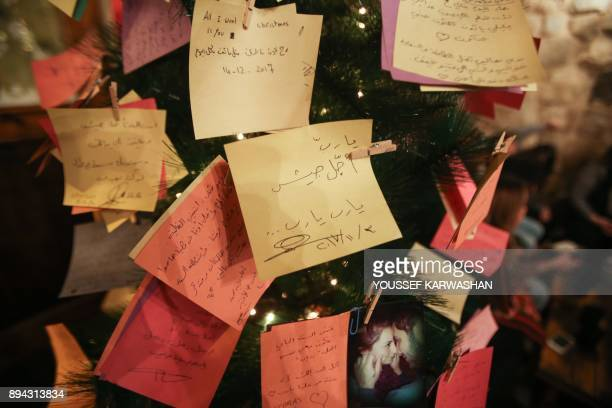 A picture taken on December 17 2017 shows New Year wishes written on cards hanging on a Christmas tree in the Zeriab coffee shop in the Syrian...