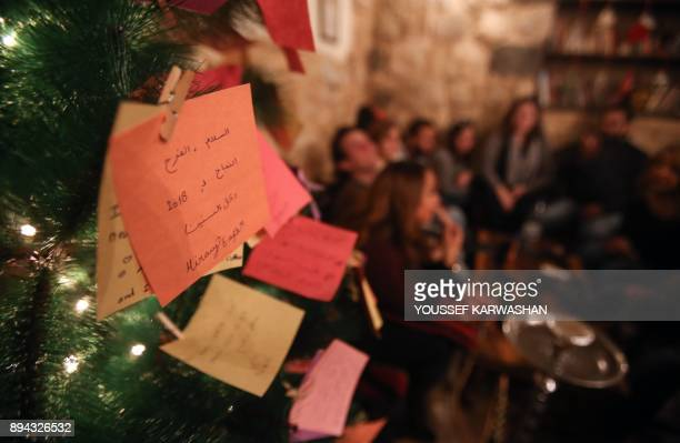 A picture taken on December 17 2017 shows New Year wishes written on cards hanging on a Christmas tree in a coffee shop in the Syrian capital...