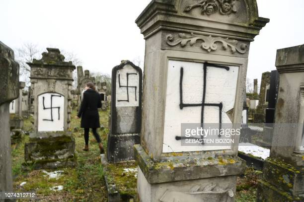 A picture taken on December 17 2018 in Herrlisheim shows jewish headstones tagged with swastika symbol at a Jewish cemetery eastern France 37...