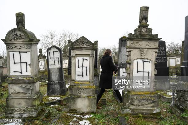 TOPSHOT A picture taken on December 17 2018 in Herrlisheim shows jewish headstones tagged with swastika symbol at a Jewish cemetery eastern France 37...