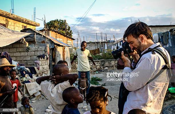 A picture taken on December 2 shows freelance Spanish photographer Ricardo Garcia Vilanova taking pictures of children in Port Au Prince the capital...