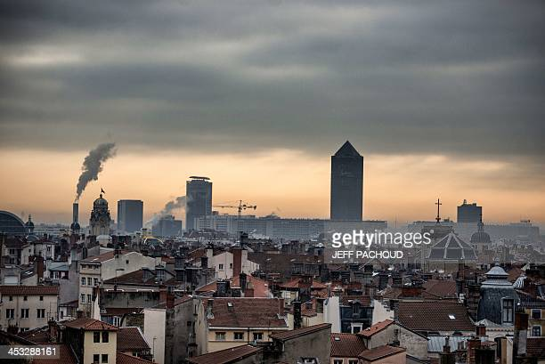 Picture taken, on December 2 shows the sun rising over Lyon with La Part-Dieu tower . AFP PHOTO / JEFF PACHOUD