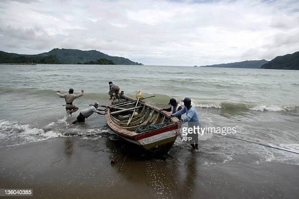 A picture taken on December 20 2011 shows Indonesian fishermen setting out to sea in their wooden boat from the fishing village of Prigi while...
