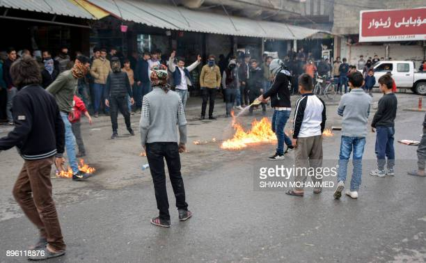 A picture taken on December 20 2017 shows a protester pouring oil on a fire in a street during a demonstration against political corruption in the...