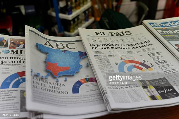 A picture taken on December 21 2015 in Barcelona shows the front covers of Spanish newspapers 'ABC' and 'El Pais' displaying titles pictures and...
