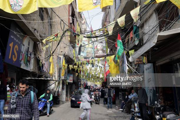A picture taken on December 21 2017 shows a view of posters showing Palestinian leaders and Fatah flags hanging in a street in the Burj alBarajneh...