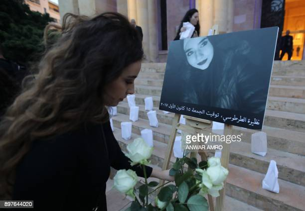 A picture taken on December 23 2017 shows a Lebanese woman placing a rose next to a portrait of a victim of genderbased violence during a candle...
