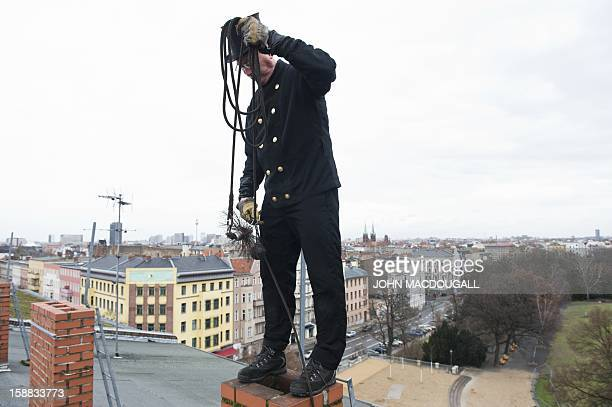 COLE Picture taken on December 27 2012 shows master chimneysweep Norbert Skrobek as he demonstrates his trade using a coiledwire brush on a rooftop...