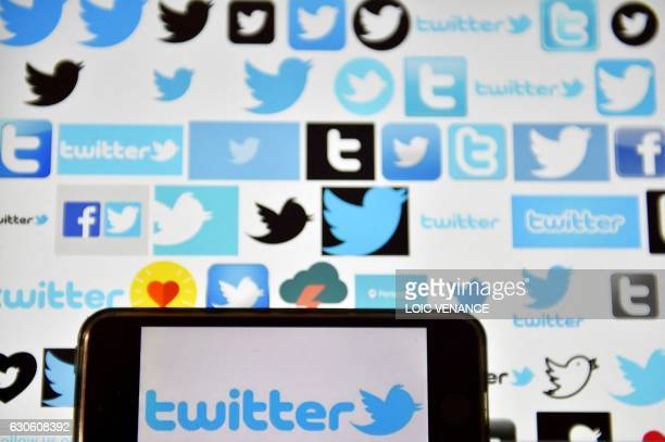 A picture taken on December 28 2016 in Vertou western France shows logos of US online news and social networking service Twitter / AFP PHOTO / LOIC...