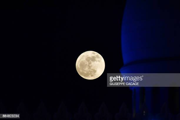 A picture taken on December 3 2017 shows a 'supermoon' rising over the Sheikh Zayed Grand Mosque in the UAE capital Abu Dhabi / AFP PHOTO / GIUSEPPE...