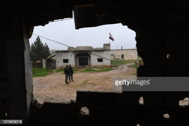 A picture taken on December 30 shows a Syrian national flag flying over a building as regime forces gather in the southern countryside of the...
