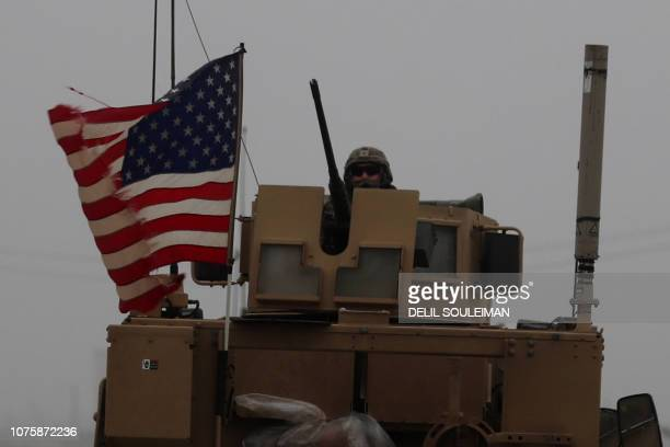 A picture taken on December 30 shows a US soldier riding an armoured personnel carrier as a line of US military vehicles patrol Syria's northern city...