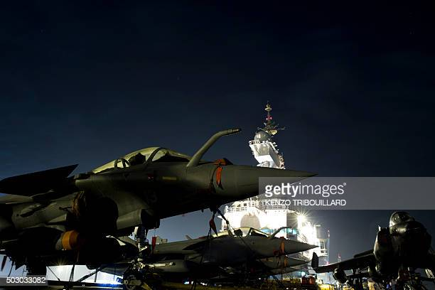 A picture taken on December 31 2015 in Manama shows French army Rafale figther jets parked on the flight deck of France's Charles de Gaulle aircraft...