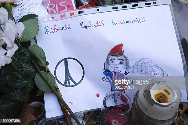 A picture taken on December 4 2015 shows a child's drawing of the French revolutionary icon 'Marianne' beside a rendering of the 'Peace For Paris'...
