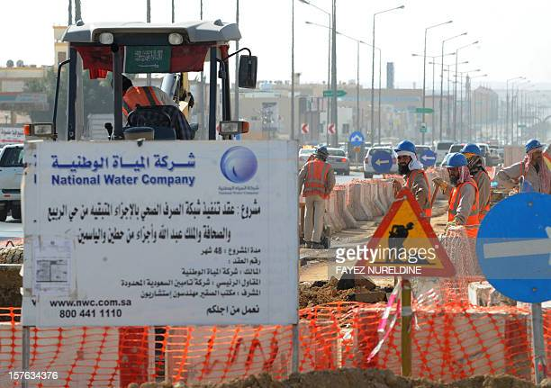 A picture taken on December 4 shows Asian laborers of the Saudi National Water Company working at a construction site in a road in the capital Riyadh...