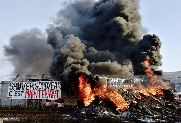 A picture taken on December 5 2013 shows burning tyres in front the US Goodyear tyremaker site in Amiens northern France following a demonstration of...