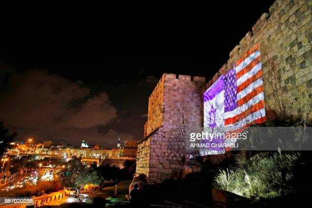 A picture taken on December 6 2017 shows a giant US flag screened alongside Israel's national flag by the Jerusalem municipality on the walls of the...