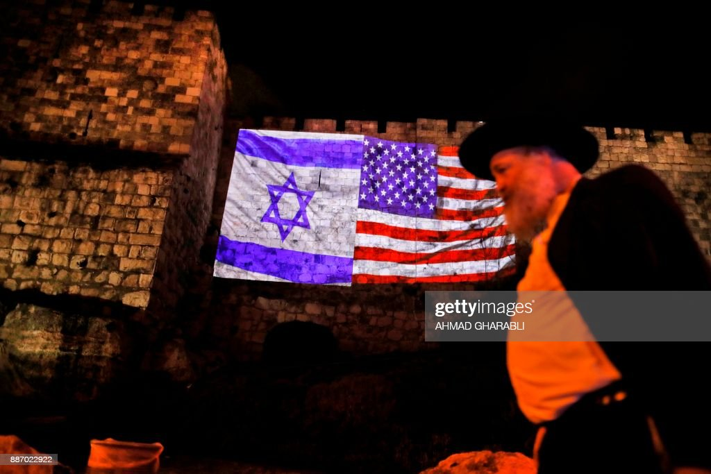 TOPSHOT - A picture taken on December 6, 2017 shows a giant US flag screened alongside Israel's national flag by the Jerusalem municipality on the walls of the old city. US President Donald Trump recognized the disputed city of Jerusalem as Israel's capital on December 6, 2017, and kicked off the process of relocating the US embassy there from Tel Aviv. The old city lies in the eastern part of Jerusalem which was under Jordanian control from Israel's creation in 1948 until Israeli forces captured it during the 1967 Six-Day War, and Israel later annexed it in a move not recognised by the international community. / AFP PHOTO / Ahmad GHARABLI