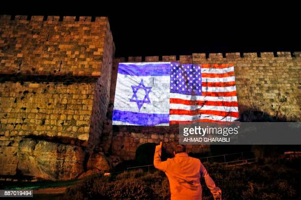 A picture taken on December 6 2017 shows a man gesturing before a giant US flag screened alongside Israel's national flag by the Jerusalem...