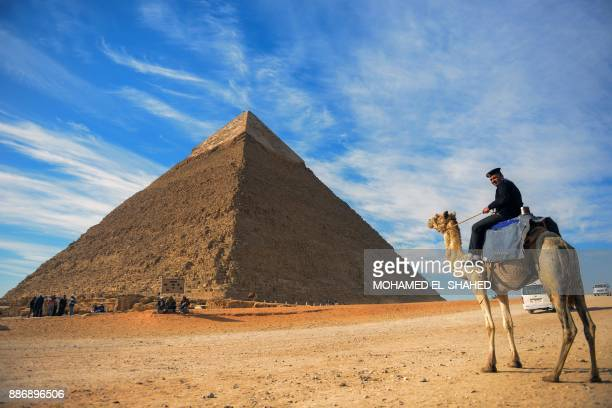 A picture taken on December 6 2017 shows an Egyptian policeman riding a camel near the pyramid of Khafre on the Giza Plateau on the southwestern...