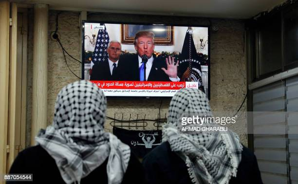 TOPSHOT A picture taken on December 6 2017 shows Palestinian men watching an address given by US President Donald Trump at a cafe in Jerusalem US...