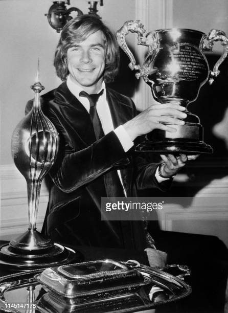 Picture taken on December 8, 1976 at London showing the 1976 world champion British racing driver James Hunt showing his trophy.