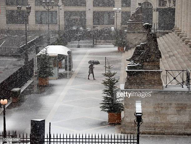 A picture taken on December 8 2010 in Paris shows a woman protecting herself from the snow under an umbrella as she walks towards Palais Brongniart...