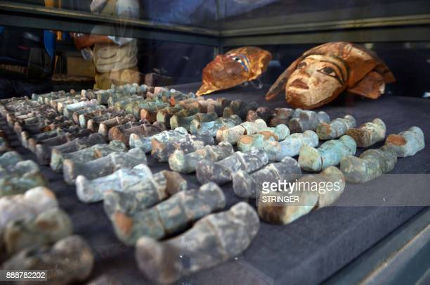 A picture taken on December 9 2017 shows ancient Egyptian wooden funerary masks and small statuettes found in and retrieved from the newly discovered...