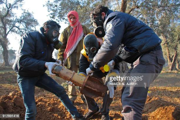 A picture taken on February 1 shows members of the Civil defence removing the remnants of a rocket reportedly fired by regime forces on the outskirts...