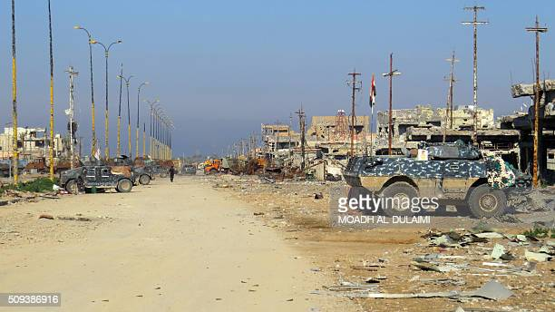 TOPSHOT A picture taken on February 10 2016 shows armoured vehicles of Iraqi progovernement forces in front of damaged buildings in the Saida area in...