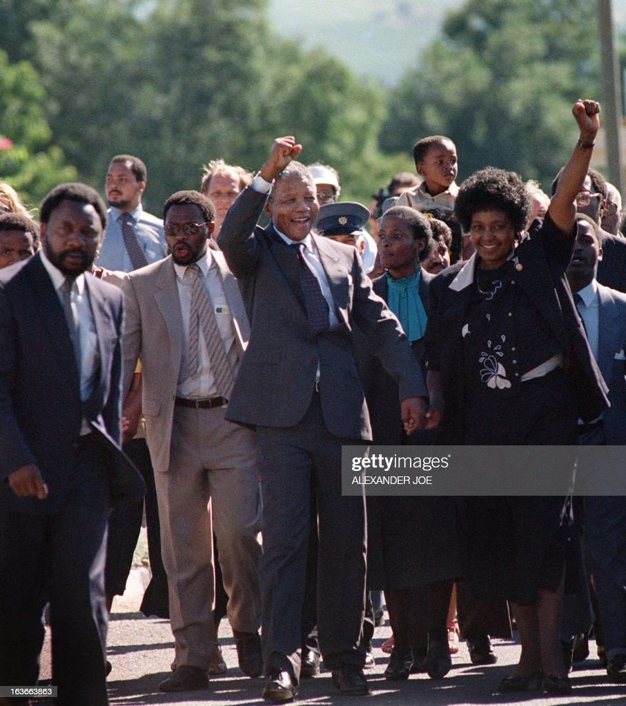 A picture taken on February 11, 1990 shows Nelson Mandela (C) and his then-wife anti-apartheid campaigner Winnie raising their fists and saluting cheering crowd upon Mandela's release from the Victor Verster prison near Paarl. Rolihlahla Dalibhunga Mandela, affectionately known by his clan name 'Madiba', became commander-in-chief of Umkhonto weSizwe (Spear of the Nation), the armed underground wing of the African National Congress, in 1961, and the following year underwent military training in Algeria and Ethiopia. After more than a year underground, Mandela was captured by police and sentenced in 1964 to life in prison during the Rivonia trial, where he delivered a speech that was to become the manifesto of the anti-apartheid movement. Mandela started his prison years in the notorious Robben Island Prison, a maximum security prison on a small island 7Km off the coast near Cape Town. In April 1984 he was transferred to Pollsmoor Prison in Cape Town and in December 1988 he was moved the Victor Verster Prison near Paarl. While in prison, Mandela flatly rejected offers made by his jailers for remission of sentence in exchange for accepting the bantustan policy by recognising the independence of the Transkei and agreeing to settle there. Again in the 'eighties Mandela rejected an offer of release on condition that he renounce violence. Prisoners cannot enter into contracts. Only free men can negotiate, he said, according to ANC reports. AFP PHOTO FILES / ALEXANDER JOE / AFP PHOTO / FILES / Alexander JOE