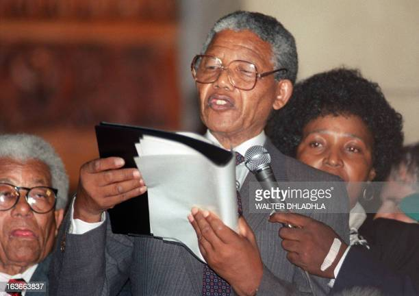 A picture taken on February 11 1990 shows Nelson Mandela flanked by hi thenwife antiapartheid campaigner Winnie giving his first speech in Capetown...