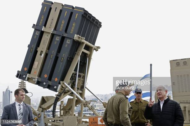 Picture taken on February 12 shows Israeli Prime Minister Benjamin Netanyahu discussing with soldiers as he stands near a naval Iron Dome defence...