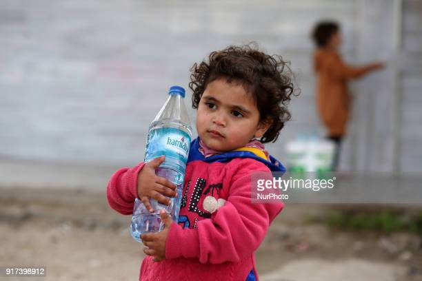 A picture taken on February 12 shows the daughter of Fadel alDeree fills a water bottle at a mosque near their tent in the middle of Gaza City The...