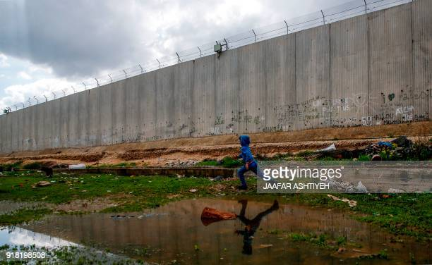 TOPSHOT A picture taken on February 14 2018 shows a Palestinian boy running between water puddles and Israel's controversial separation barrier in...