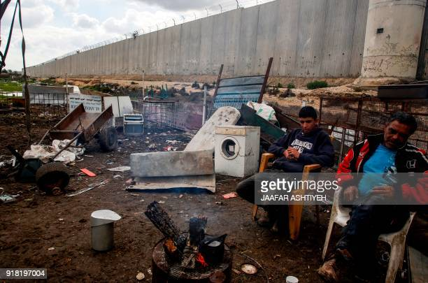 TOPSHOT A picture taken on February 14 2018 shows Palestinian farmers sitting by a fire next to junk and rundown appliances near Israel's...