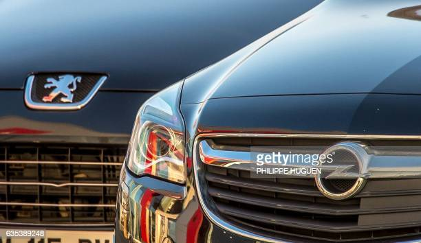A picture taken on February 15 2017 shows the logo of German car maker Opel on a car next to a car with the logo of French car maker Peugeot in Lille...