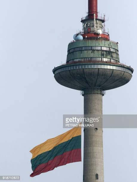 A picture taken on February 15 2018 in Vilnius shows a giant national flag displayed next to a TV tower as part of the festivities marking 100 years...