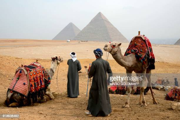 TOPSHOT A picture taken on February 15 2018 shows Egyptian tour guides preparing a caravan of camels for tourists as they sit across the Giza plateau...