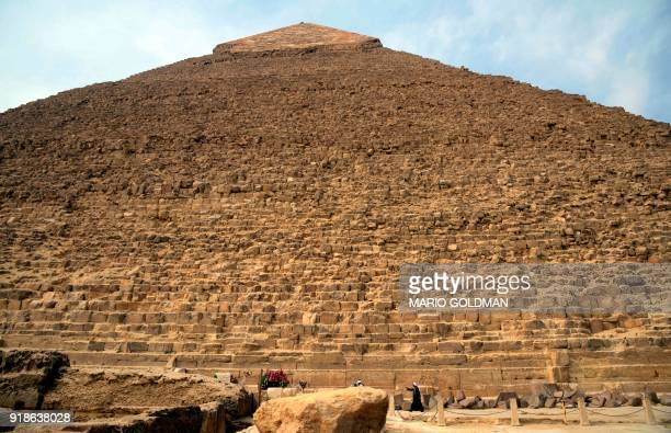 A picture taken on February 15 2018 shows Egyptian tour guides standing at the base of the Pyramid of Khafre at the Giza pyramids complex on the...