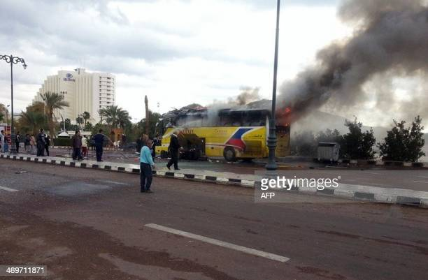 A picture taken on February 16 shows flames rising from the wreckage of a tourist bus at the site of a bomb explosion in the Egyptian south Sinai...