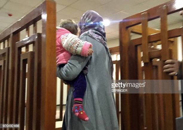 TOPSHOT A picture taken on February 19 shows French Jihadist Melina Boughedir carrying her son as she arrives to court in the Iraqi capital Baghdad...
