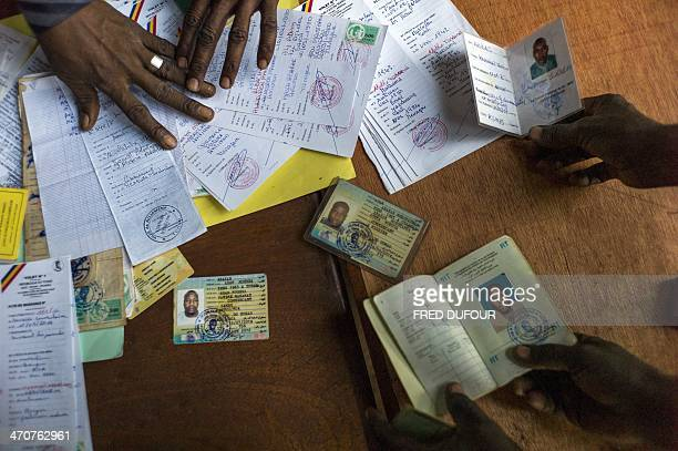 A picture taken on February 20 2014 shows Chadian people displaying their identity cards on a table at the Mpoko Muslim refugee camp in Bangui...